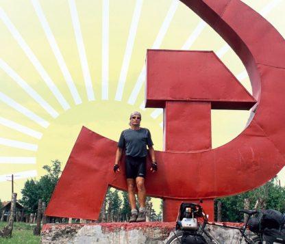 """Ausschnitt vom Titelbild zu Diashow """"Der Sonne entgegen - Wladiwostok"""", Reiseimpressionen von Thomas Meixner. Zu sehen sind der Autor mit Fahrrad vor Hammer und Sichel in Russland."""
