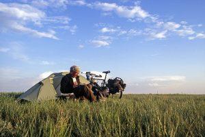"""Foto zu Diashow """"Der Sonne entgegen - Wladiwostok"""", Reiseimpressionen von Thomas Meixner. Zu sehen sind der Autor sitzend vor seinem Zelt in der Steppe Russlands. Neben seinem Steppenlager steht sein Fahrrad."""
