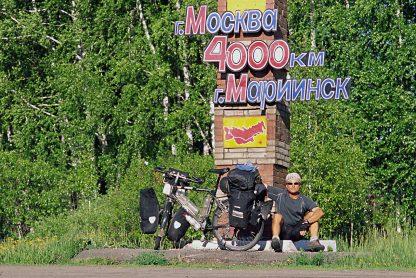 """Foto zu Diashow """"Der Sonne entgegen - Wladiwostok"""", Reiseimpressionen von Thomas Meixner. Zu sehen sind der Autor mit Fahrrad vor einem gemauerten Wegweiser mit dem Hinweiß """"4000 Km von Mariinsk nach Moskau""""."""